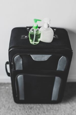 travel safety and hygiene in times of virus outbreak, packing a suitcase with hand sanitizer and liquid soap bottles Zdjęcie Seryjne