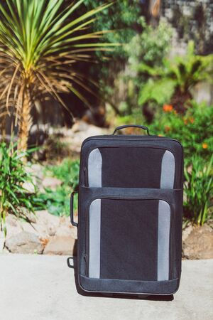 concept of summer holidays, suitcase with tropical garden bokeh behind it concept of travelling to warm tropical destinations