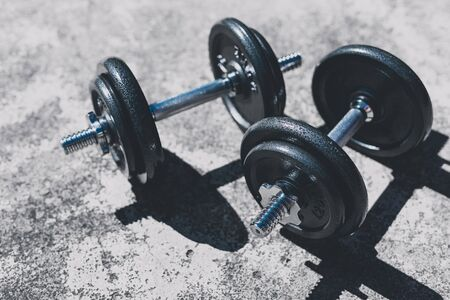keeping fit and exercising outdoor or at home, set of heavy dumbbells on concrete path in a backyard Stock Photo - 142539780