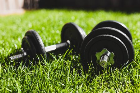 keeping fit and exercising outdoor or at home, set of heavy dumbbells on green grass lawn in a backyard under direct sunlight Stock Photo - 142539846