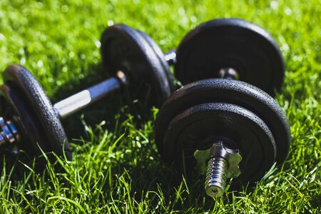 keeping fit and exercising outdoor or at home, set of heavy dumbbells on green grass lawn in a backyard under direct sunlight Stock Photo - 142539849