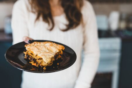 healthy homemade plant-based food recipes, woman holding piece of vegan lentil and nutritional yeast shepherd's pie towards the camera Stock Photo - 142539860