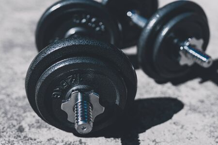 keeping fit and exercising outdoor or at home, set of heavy dumbbells on concrete path in a backyard Stock Photo - 142540026