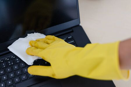 practice good hygiene against viruses and bacteria, hand with cleaning gloves disinfecting laptop keyboard with wipe Stock Photo - 142540034