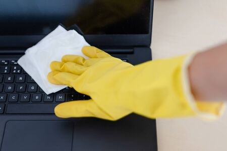 practice good hygiene against viruses and bacteria, hand with cleaning gloves disinfecting laptop keyboard with wipe