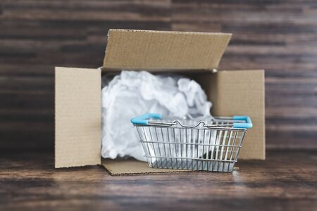 concept of home delivery of groceries and online shopping, open parcel with shopping basket inside of it Stock Photo - 142510182