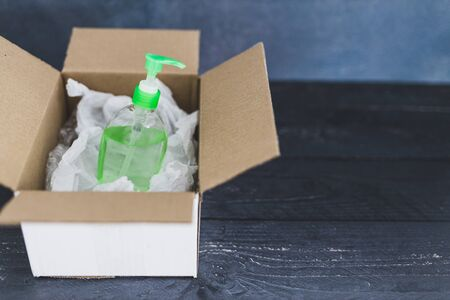 hygiene against viruses and bacteria concept, hand sanitizer bottle inside delivery parcel symbol highly sought after products in times of self-isolation and quarantines Stock Photo - 142540126