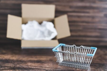 concept of home delivery of groceries and online shopping, open parcel with shopping basket inside of it Stock Photo - 142510800