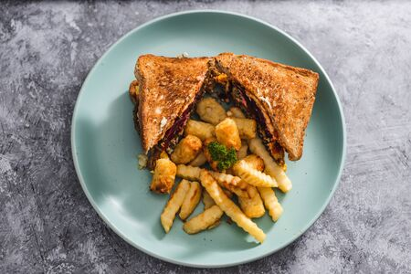 healthy plant-based food recipes concept, vegan club sandwichs with veggie patties and chips Foto de archivo