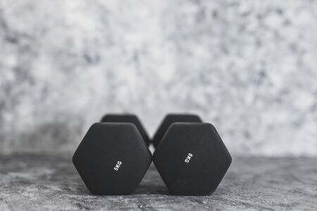 sport and fitness gear, set of black dumbbells on concrete shot at shallow depth of field