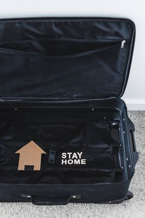 isolation and travel restrictions to flatten the curve against the covid-19 virus outbreak, open empty suitcase with nothing packed inside except for Stay Home message and house icon next to it Stock Photo
