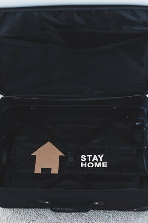 isolation and travel restrictions to flatten the curve against the covid-19 virus outbreak, open empty suitcase with nothing packed inside except for Stay Home message and house icon next to it Stock fotó