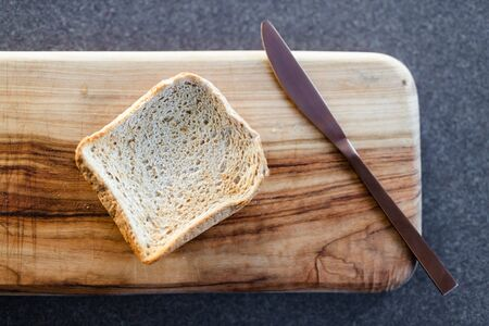 healthy food ingredients, piece of toasted bread on cutting board with knife next to it