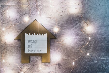 social distancing concept, Stay Home message on house icon surrounded by fairy lights shot at shallow depth of field with desaturated tones Stok Fotoğraf