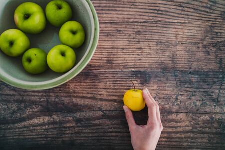 healthy plant-based food ingredients concept, bowl of green apples and hand holding a smaller yellow one next to it Stock Photo - 148600776