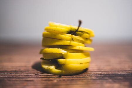 healthy plant-based food ingredients concept, yellow apples cut into stacked slices