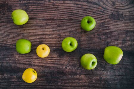 healthy plant-based food ingredients concept, multitude of green and yellow apples scattered on wooden table Stock Photo - 148600782