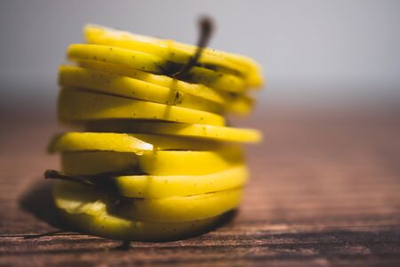 healthy plant-based food ingredients concept, yellow apples cut into stacked slices Stock Photo