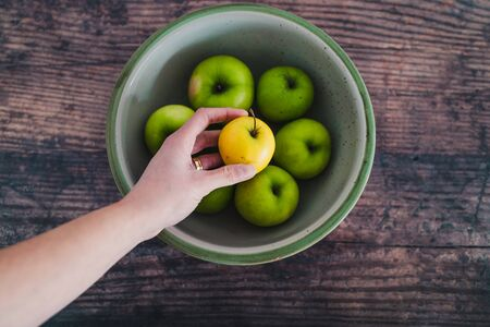 healthy plant-based food ingredients concept, bowl of green apples and hand holding a smaller yellow one next to it Stock Photo - 148600787