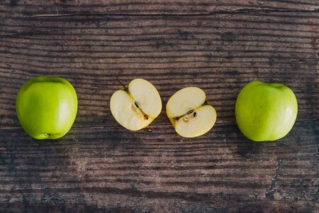 healthy plant-based food ingredients concept, apple halves on wooden table next to whole apples Stock Photo - 148600790