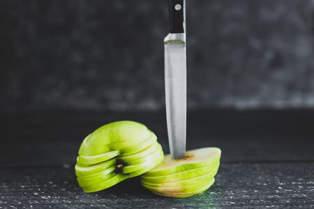 healthy plant-based food ingredients concept, green apple cut into thin equal slices stacked into two halves with knife Stock Photo - 148600767