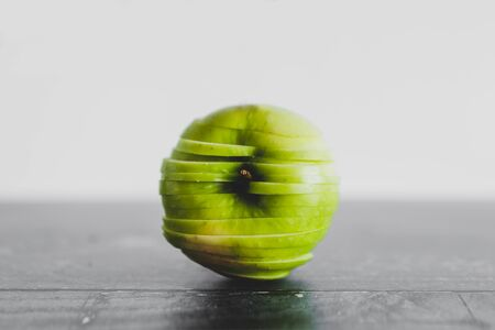 healthy plant-based food ingredients concept, green apple cut into thin equal slices stacked to maintain its original shape Stock Photo - 148600768