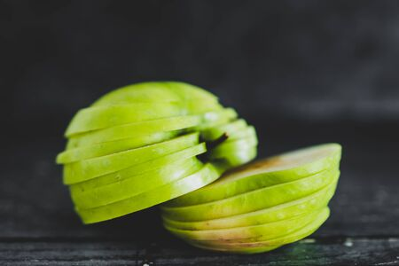 healthy plant-based food ingredients concept, green apple cut into thin equal slices stacked into two halves Stock Photo - 148600772
