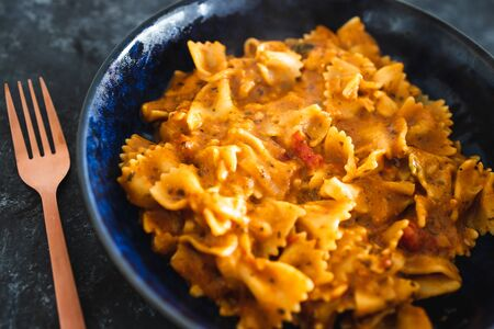 healthy plant-based food recipes concept, vegan bowtie pasta with red pesto and mediterranean vegetables Stock Photo - 148788187