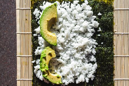 healthy plant-based food recipes concept, vegan avocado sushi getting prepared on roller Stock Photo - 148863131