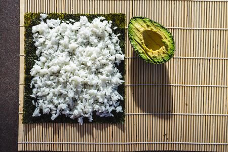 healthy plant-based food recipes concept, vegan avocado sushi getting prepared on roller Stock Photo - 148862977