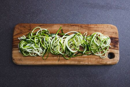 simple food ingredients concept, zucchini noodles on wooden cutting board Stock Photo - 148862763