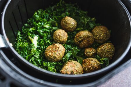 healthy plant-based food recipes concept, falafels and kale chips in air fryer Stock Photo - 148962249
