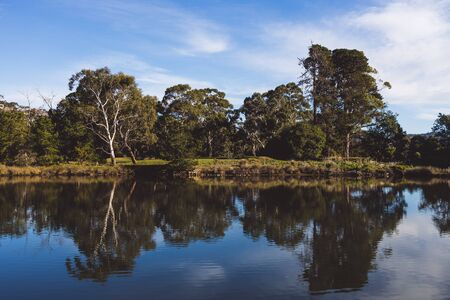 Tasmanian landscape of the Browns River with eucalyptus gum trees reflected on the water and with contrasty sky Stock Photo - 148961533