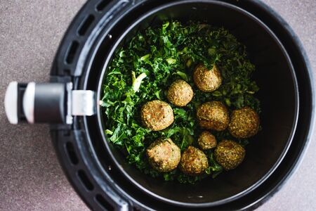 healthy plant-based food recipes concept, falafels and kale chips in air fryer Stock Photo - 148961983