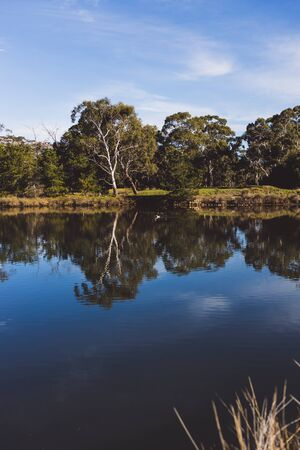 Tasmanian landscape of the Browns River with eucalyptus gum trees reflected on the water and with contrasty sky Stock Photo - 148961657