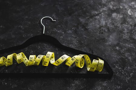 fashion industry and risks of eating disorders concept, velvet hanger with yellow measuring tape on it on black background