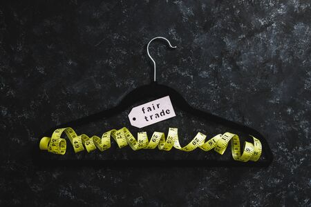 fashion industry and ethical products concept, velvet hanger with yellow measuring tape and Fair Trade label on it on black background
