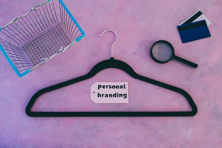 style and fashion industry concept, velvet clothes hanger on pink desk with shopping cart and personal branding label next to credit cards