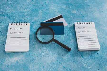 managing money and finance concept, planned expenses vs actual expenses notepads side by side with credit cards and magnifying glass on blue desk 版權商用圖片
