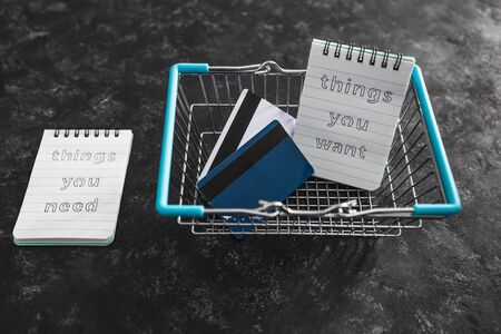 budgeting and shopping concept, things you need vs things you want notepads in shopping basket with credit cards