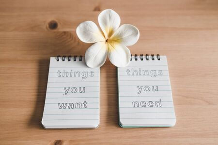 lifestyle and psychological insights concept, notepads with titles Things you need vs things you want side by side on desk ready for meditation