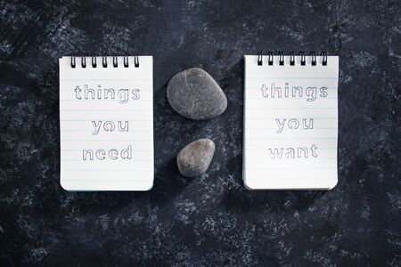 meditation and psychological insights concept, notepads with titles Things you need vs things you want side by side on desk dark with zen pebbles Stock fotó