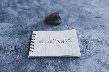 self-care and mental health concept, notepad with text Meditate next to zen pebbles on grey concrete surface