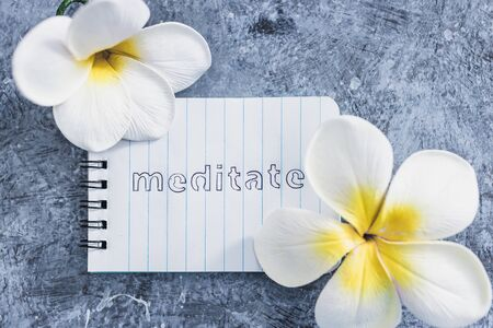 self-care and mental health concept, notepad with text Meditate next to tropical flowers on grey concrete surface Stok Fotoğraf