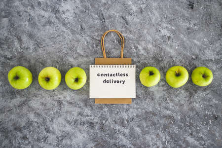 the new normal after covid-19, Contactless Delivery text on notepad among apples and with shopping bag concept of groceries shopping during quarantine or lockdown Standard-Bild - 151422469