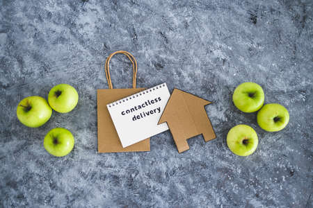the new normal after covid-19, Contactless Delivery text on notepad among apples and with shopping bag and house icon concept of groceries shopping during quarantine or lockdown Standard-Bild