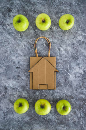 home delivery and groceries shopping concept, shopping bagwith house icon among apples symbol of healthy nutrition