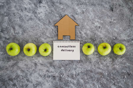 the new normal after covid-19, Contactless Delivery text on notepad among apples and with house icon concept of groceries shopping during quarantine or lockdown Standard-Bild