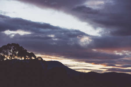 sunset sky with beautiful clouds rolling over the hills of Tasmania, Australia Stock Photo