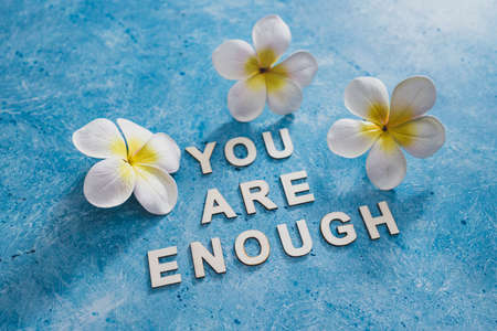 mental health and self-worth concept, You are enouugh text with flowers and blue background Banco de Imagens